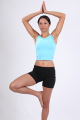 Beautiful woman in yoga tree pose during exercise