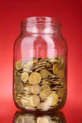 coins in money jar on red background