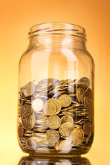 coins in money jar on yellow background