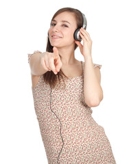 young woman in headphones listening music, pointing you