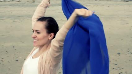 Woman with waving sarong running along the beach, shot at 60fps