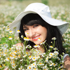 young happy girl in the chamomile field