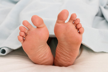 A woman's feet under a blanket