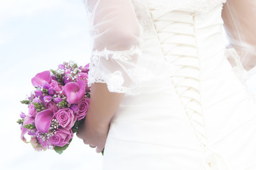 bride holding bouguet with purple and pink flowers