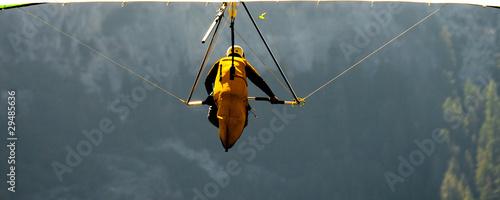 Leinwandbild Motiv Hang-gliding over a valley