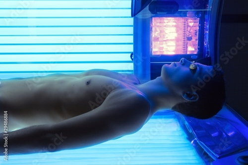 Tanning solarium young man laying