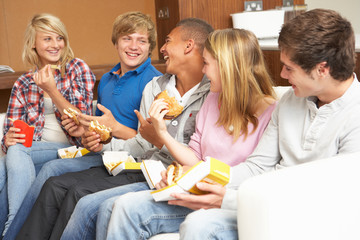 Group Of Teenage Friends Sitting On Sofa At Home Eating Fast Foo
