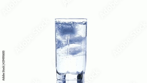 Water pouring into a glass with ice cubes isolated on white, HD