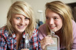 Two Teenage Girls Sitting On Sofa At Home Drinking Alcohol