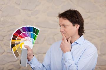 mann plant neuen anstrich mit farbfächer