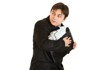 Wary businessman hugging briefcase with money in hands