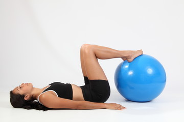 Athletic young sports woman working out with exercise ball