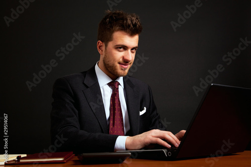 Portrait of a businessman typing on the laptop. Black background