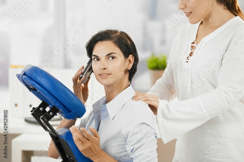 Occupied businesswoman getting massage - 29521802