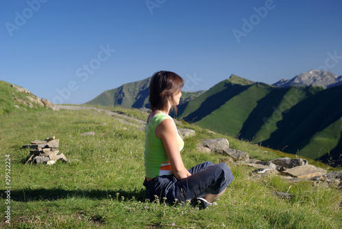Woman sitting on grass in mountains relaxing