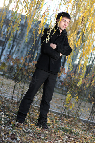 a guy in a black coat on green willow autumn
