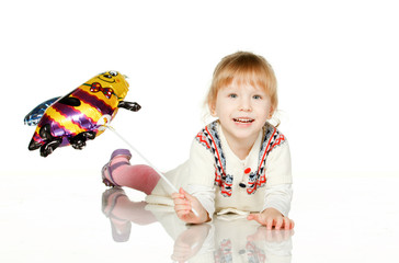 Smiley kid lying on the floor with balloon bee; isolated