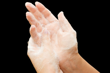 Female hands in soapsuds isolated on black