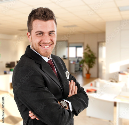 Smiling handsome businessman with office on the background