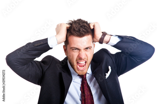Portrait of an angry  businessman holding hair.White background