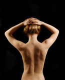 Nude young woman from back with arms raised