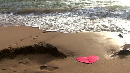 red heart cut in two pieces been washed away by the sea