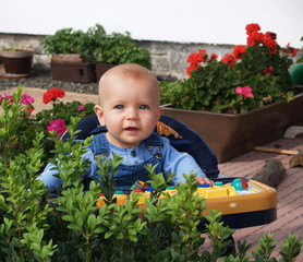 Little girl in baby-walker on terrace with flowers