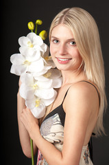 Young beautiful girl with orchid on black background