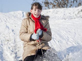 Teen girl sledding from a hill