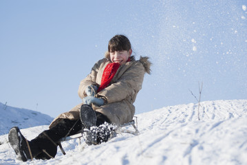 Teen girl sledding from a hill