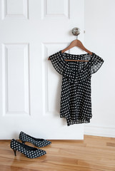 Polka dot shoes and stylish blouse on a hanger