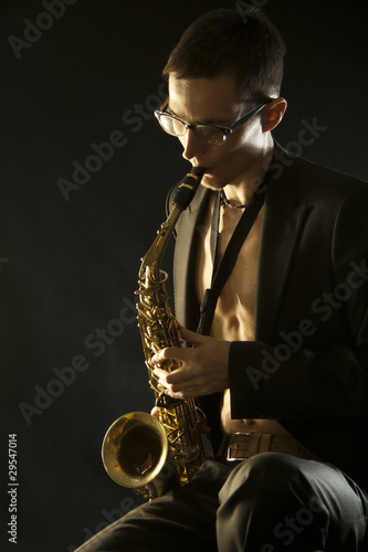 The young jazzman plaing a saxophone on black