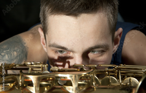 closeup young jazz man look on saxophone