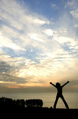 Silhouette of young happy girl at sunset looking out to sea with