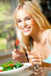 Portrait of young happy smiling woman eating salad at home