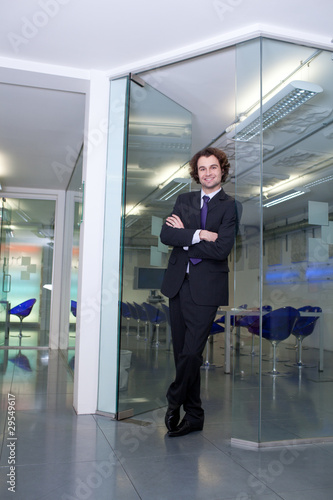 Confident businessman standing with crossed arms