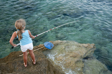 Little girl fishing  at the beach