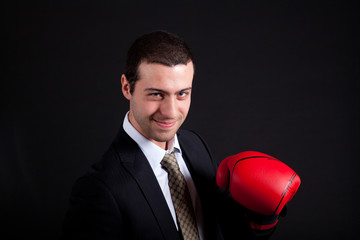 Businessman wearing boxing gloves over black background