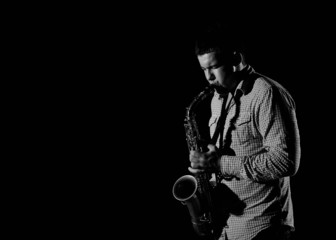 Young handsome man playing music on saxophone. black background