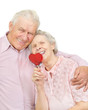 happy old couple with red heart-shaped candy