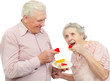 happy old couple with red and yellow heart-shaped cookies