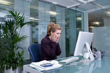 Shocked businesswoman at desk in office