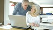 Senior couple working at home on laptop computer