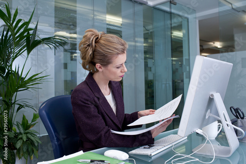 Businesswoman reading documents at desk in office