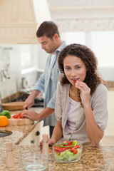 Woman eating while her husband is cooking