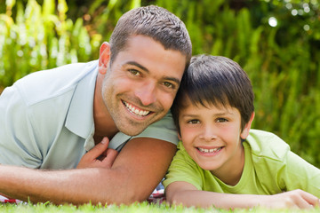 Father with his son lying down in the garden