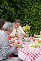 Happy family eating in the garden