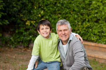 Grandfather with his grandson looking at the camera in the garde