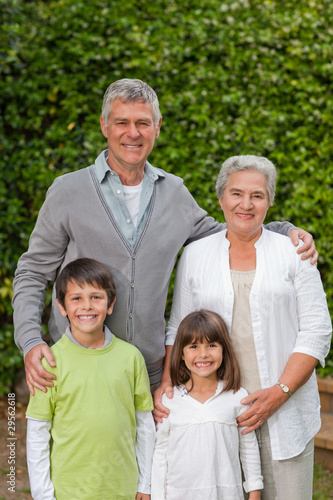 Grandparents with their children looking at the camera in the ga