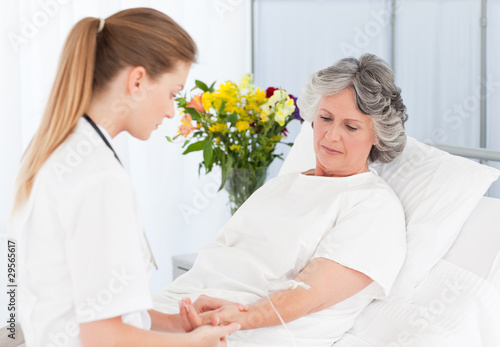 Nurse putting a drip on the arm of her patient
